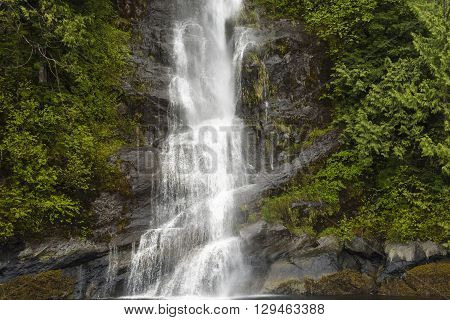 A waterfall falling down the side of a mountain in the rain forest