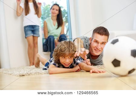 Father and son having fun with soccer ball in the living room