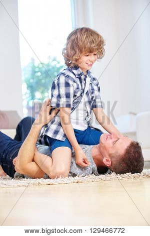 Happy father and son playing together in living room
