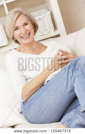 Portrait of an attractive elegant senior woman wearing jeans and relaxing at home on her sofa