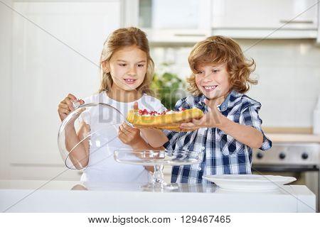 Children presenting their homemade fruitcake in the kitchen