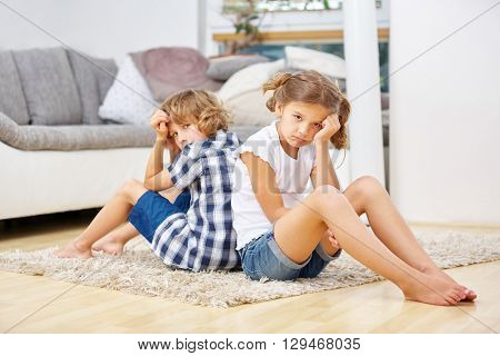 Two sad siblings sitting at home in the living room