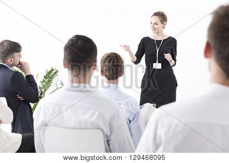 Shot of a young manager talking to a group of her coworkers and pointing at one of them