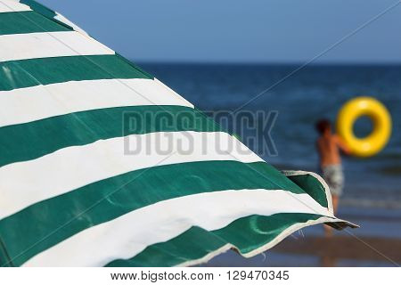 Sun Umbrellas On The Beach With A Child With A Life Preserver On The Shore