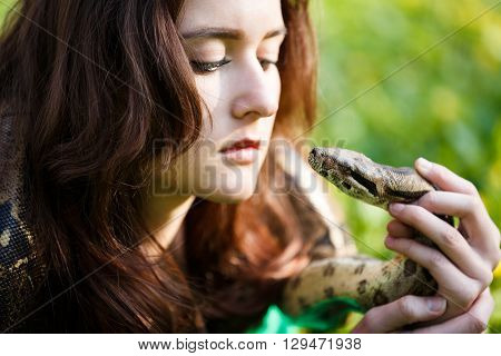 Attractive teenage girl holding the python close near the face
