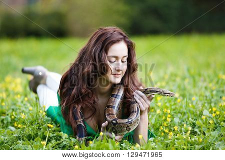 Happy smiling teenage girl lying on the green grass with python