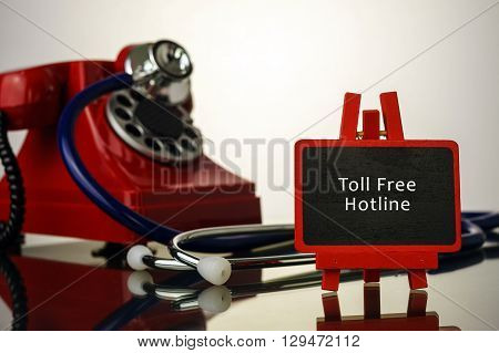 Medical Concept.phone And Stethoscope On The Table With Toll Free Hotline Words On The Board.
