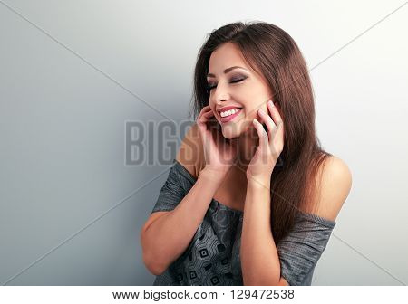 Happy Laughing Brunette Young Woman Holding The Hand At Face And Giggling On Blue Background