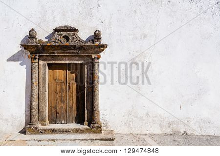 Old grungy church portal in a street of the Marvao village, Portalegre District, Alto Alentejo, Portugal. Marvao was a candidate to World Heritage Site by UNESCO.