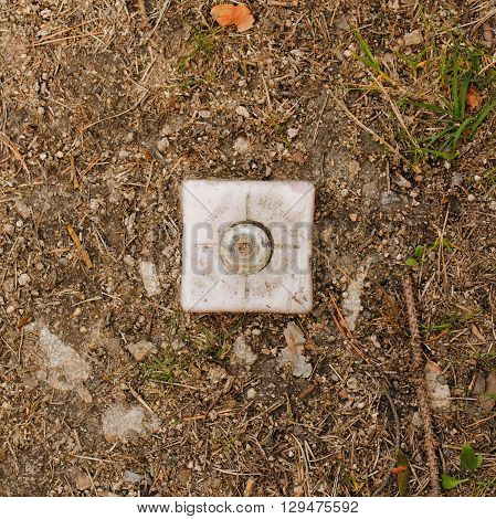 Square photo of border marker. Plastic border marker separating land plots. Plastic cube in soil. Marker placed in the earth. Dividing mark of land. Boarder between land plots.