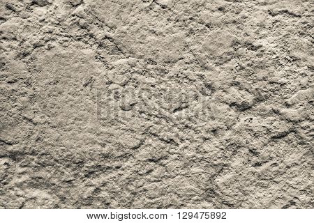 bumpy texture of a concrete or stone surface of beige color for abstract background and for wallpaper