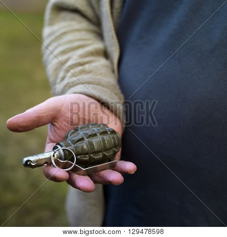 Male hand holding grenade outdoor closeup with selective focus