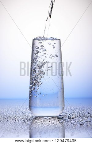 Water Pouring Into Full Drinking Glass With Reflection