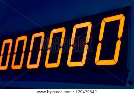 Electronic digital numbers show zero on blue wall background