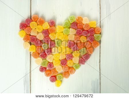 A heart made of many vibrant multicolored gum drops (yellow red orange and green) shot from above on light blue wooden background texture with copyspace