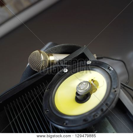 Microphone laid on an amplifier loudspeaker on the blurred foreground