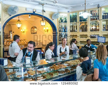 Belem Portugal - April 28 2014: A group of tourists buying the famous Pasteis de Belem (Pastries of Belem). The pastries of this shop are well known around the world and a touristic destination in Belem Portugal.