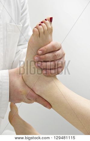 physical therapist providing foot massage to woman in office
