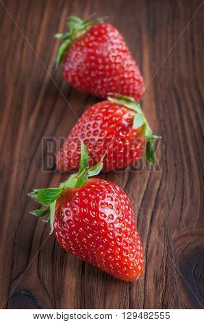 Ripe fresh strawberries on a wooden table