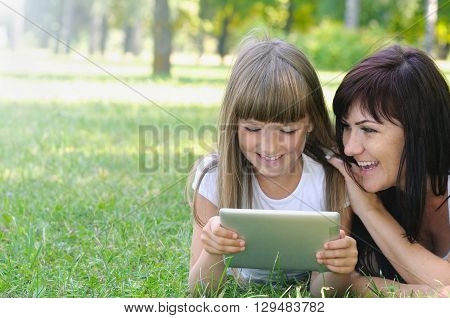 Happy Girl And Her Mother Having Fun On The Grass In The Park