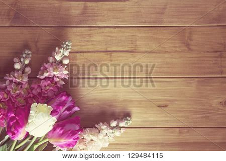 overhead of flowers arranged on a wooden top