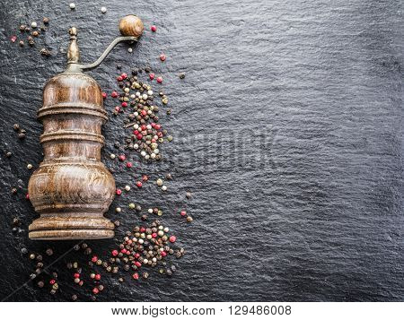 Colorful peppercorns and old pepper mill on the black background.