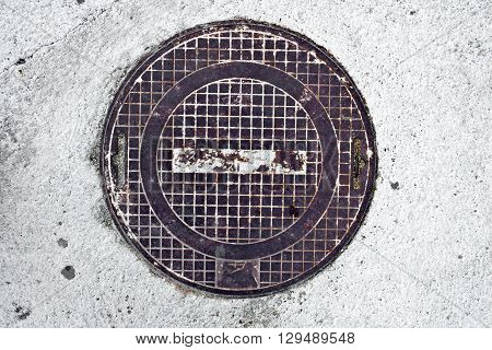 Metal rusty manhole cover in white concrete