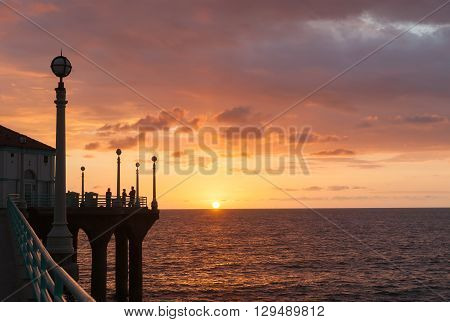 Manhattan Beach, California, USA - October 6, 2015; Silhouettes of people gathered to experience sunset over ocean from Manhattan Beach pier watching sunset sunset California