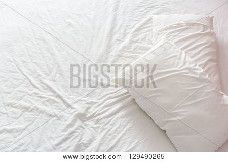 Top view of an untidy / unmade bed with white crumpled bed sheet and two messy pillows in a hotel room. An accommodations that is not neatly arranged for a new guest / customer / visitor to sleep in.