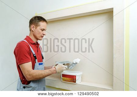 Decorative plaster coating. Man takes plaster from container.