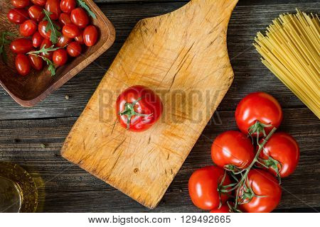 Top view food of italian cooking ingredients on rustic wooden backdrop. Tomatoes, spaghetti pasta, olive oil and arugula salad