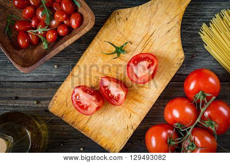 Cut tomatoes. fresh tomatoes on vine, cherry tomatoes, dry pasta, olive oil and arugula salad on rustic wooden backdrop. Top view. Preparing tomatoes for cooking with pasta, italian cuisine