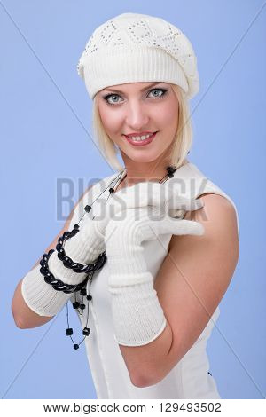 knitwear. young woman wearing a winter cap and gloves isolated on blue background