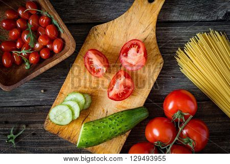 Cooking ingredients on wooden cutting board. Cut tomatoes, cucumber, fresh tomatoes on vine, cherry tomatoes, dry pasta, olive oil and arugula salad on rustic wooden backdrop. Top view food.