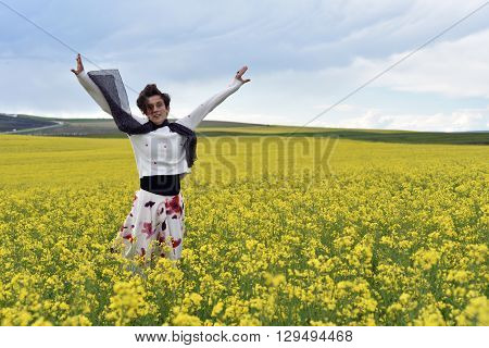 Happy Woman Jumping In The Middle Of A Canola Field