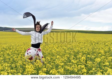 Young Woman Jumping In The Middle Of A Canola Field