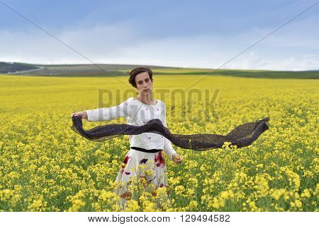 Gorgeous Young Woman Playing With Scarf In A Canola Field