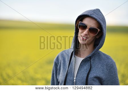 Smiling Girl In Hoodie And Sunglasses In The Outdoors
