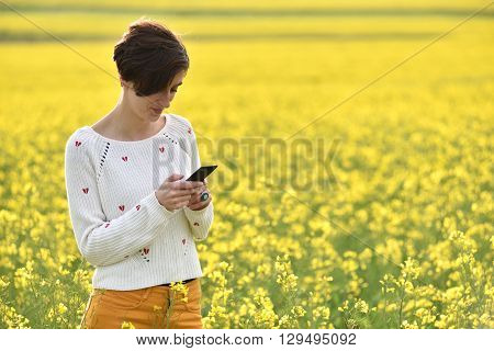 Young Hipster Girl Messaging On Her Smart Phone In The Middle Of A Canola Field