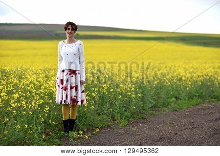 Hipster Girl In Skirt Posing Near A Canola Field