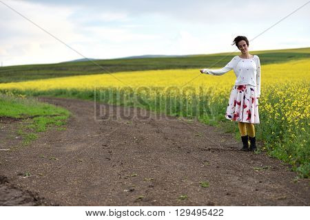 Traveler Woman In Dress Hitchhiking In The Countryside