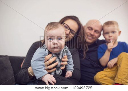 A photo of happy family sitting on the couch. Mum is holding the baby on the first plan.