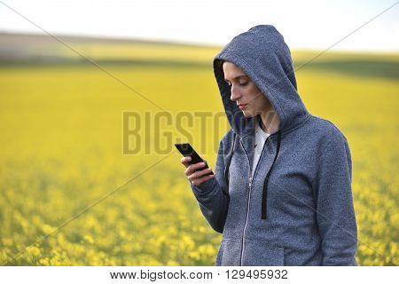 Hipster Woman In Hoodie Using Her Smart Phone In The Outdoors