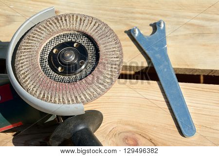 Front part of angle grinder with abrasive disc and spanner after work.