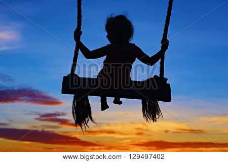Black silhouette of baby girl flying high with fun on rope swing on blue orange sunset sky background. Travel lifestyle people beach activity on summer family vacation with child in tropical island.