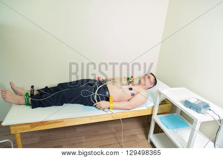 doctor  with electrocardiogram equipment making cardiogram test to male patient in hospital clinic