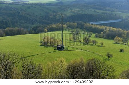 Transmitter on green meadow near highway to Germany
