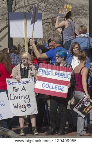 Asheville, North Carolina, USA - February 28, 2016: Crowd of Bernie Sanders supporters including Millennials citing issues of low wages and expensive education stand on a street corner holding signs and interacting with cars and passersby during a rally
