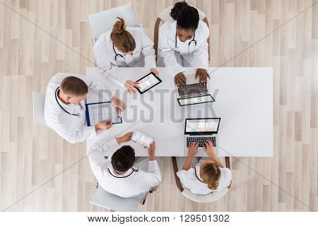 High Angle View Of Doctors With Laptop And Digital Tablet In Meeting