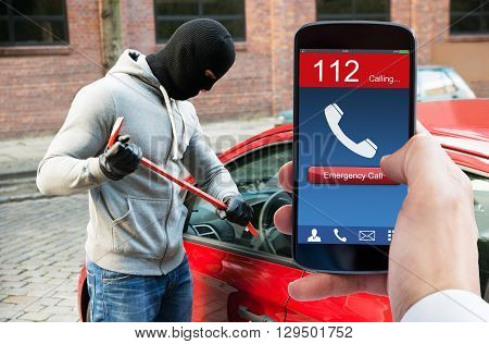Person's Hand With Emergency Call On Mobile Phone While Burglar Opening Car Door With Crowbar
